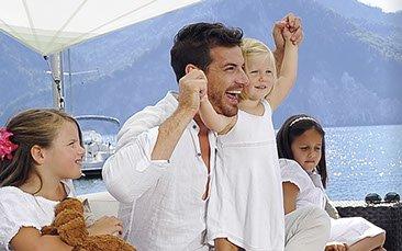Lachende Familie vor Soliday Sonnensegel