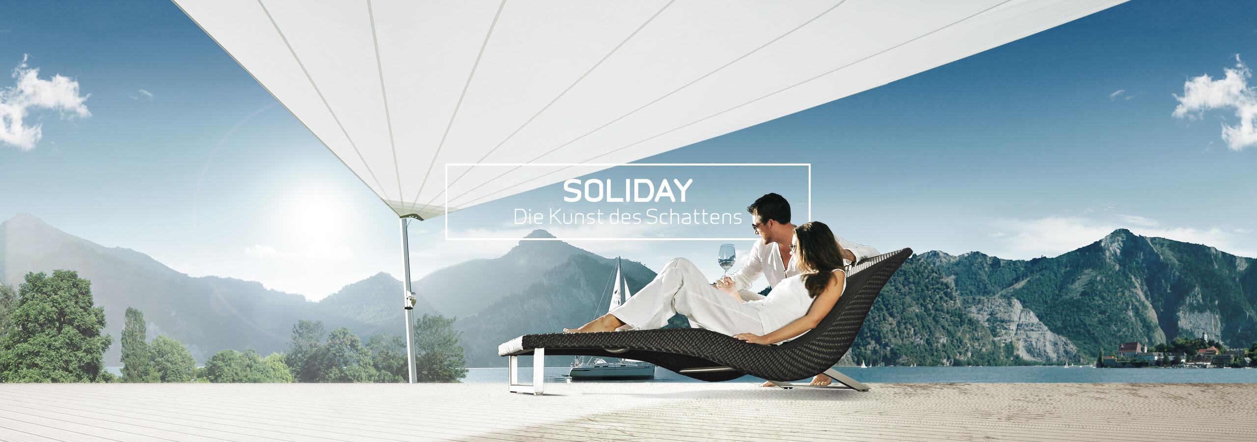 Liege unter einem aufrollbaren Sonnensegel von Soliday auf Terrasse am See